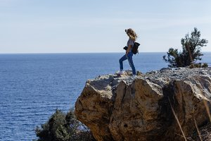 Photographer enjoying seaview and standing on high rock cliff