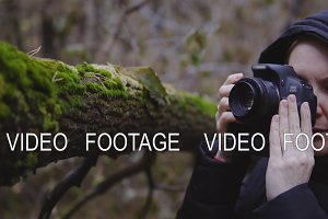 girl photographer walks through the autumn forest and takes pictures of nature. cinematic shot. slow motion