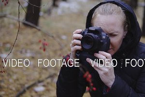 slow motion, cinematic shot. girl photographer takes photos of autumn nature in the forest. photographs a berry.