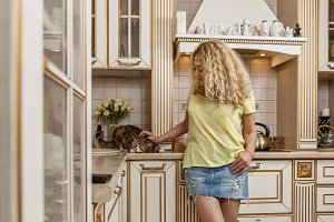 Woman and cat in kitchen.
