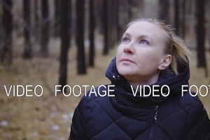 cinematic shot, slow motion. the blond girl is walking along the autumn forest in the jacket. first snow.
