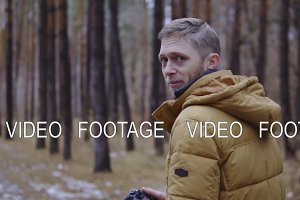 the man in the jacket walks through the autumn forest. slow motion, cinematic shot.