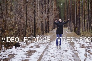 girl jumping in the forest in slow motion. enjoys the first snow of the year. autumn forest
