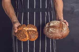 Variety of freshly baked breads in a young bakers hands. Hipster nordic baker with rye, wholewheat and white bread close up