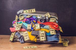Packed suitcase with travel accessories and money on wooden background