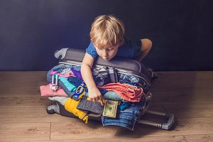 Baby boy and Travel Suitcase. Kid and Luggage Packed for Vacation Full of Clothes, Child and Family Trip