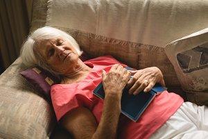 Senior woman sleeping on sofa in living room