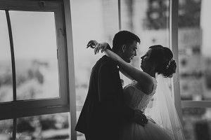 black white photo bride and groom on background clear windows