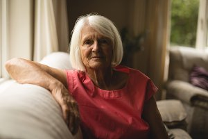 Senior woman sitting on sofa in living room