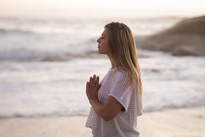 Young woman meditating at beach during sunset