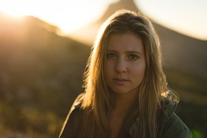 Portrait of young woman standing against mountain