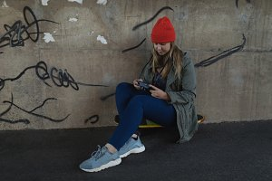 Young woman using mobile phone while sitting on skateboard