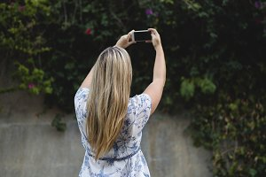 Rear view of young woman photographing with mobile phone
