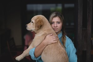 Portrait of young woman carrying Golden Retriever
