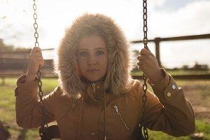 Portrait of woman wearing winter coat swinging in playground