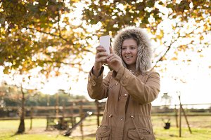 Young woman wearing winter coat taking selfie while standing at park