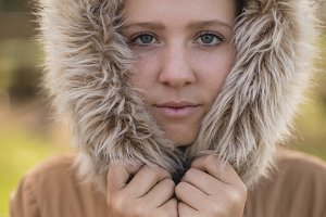 Portrait of young woman in winter coat standing at park
