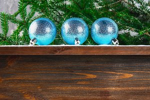 Three blue New Year balls lie on a wooden brown shelf surrounded by fir branches.