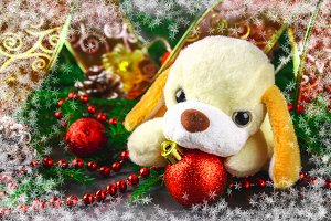 Symbol of the 2018 new year toy dog surrounded by decorative Christmas elements and fir branches.