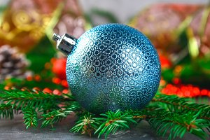 Christmas blue decorative balloon surrounded by fir branches.