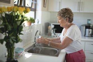 Senior woman washing glass in kitchen