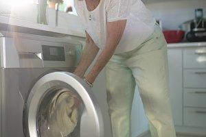 Senior woman putting clothes into washing machine