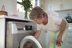 Senior woman putting clothes into washing machine