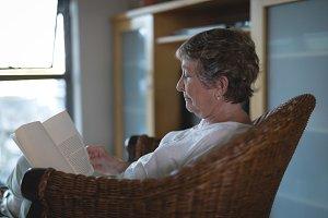 Senior woman reading novel in living room