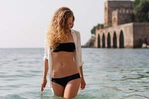 Fit blonde female in swimwear standing in sea in front of Alanya