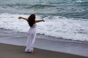 Woman wearing white dress and enjoying sea storm