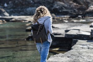 Blond woman tourist with backpack walking on rock ribbed shore