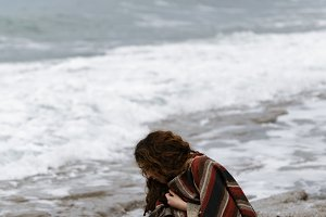 Young woman in striped poncho collecting pebbles on the beach