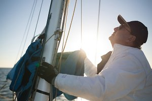 Yachtsman pulling the rope tuning the sails