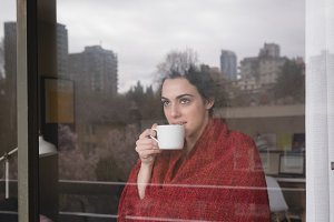 Contemplated woman with coffee cup seen through glass