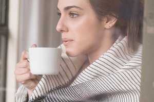 Thoughtful woman with coffee cup seen through glass