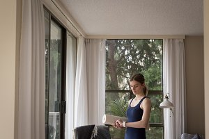 Woman looking at time while standing by window