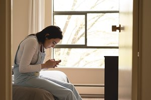Side view of woman using mobile phone while sitting on bed