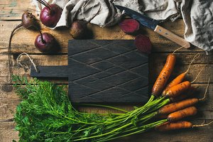Garden carrots and beetroots with dark cutting board in center
