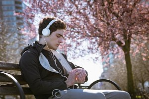 Man listening music while sitting on bench