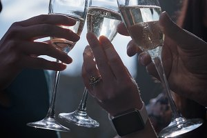 Cropped hands of business people toasting champagne flutes