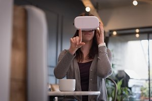 Businesswoman wearing virtual reality simulator at table