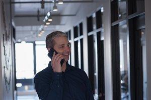 Businessman talking on phone in corridor
