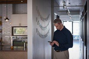 Businessman using phone in corridor