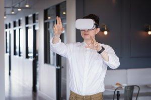 Businessman wearing virtual reality simulator in corridor