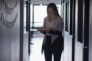 Businesswoman holding document at corridor