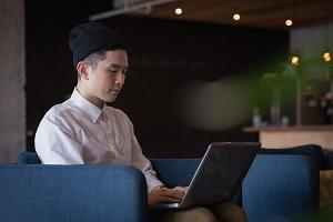 Businessman using laptop on armchair