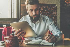 Young bearded businessman sits in cafe at table, holding tablet computer and writes in notebook. Man is working