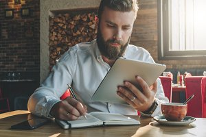 Young bearded businessman sits in cafe, home at table, looking at screen of tablet computer and writes in notebook.