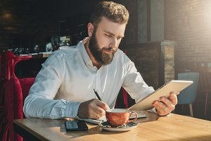 Young bearded businessman sits in cafe, home at table, uses tablet computer and writes in notebook.