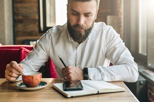 Young bearded businessman, sits in cafe, office at table, holds pen in his hand, reads information on smartphone screen